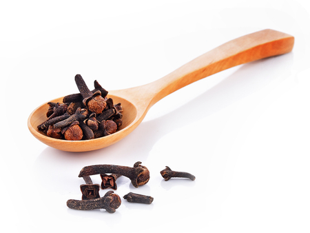 Dried cloves spoon on white background