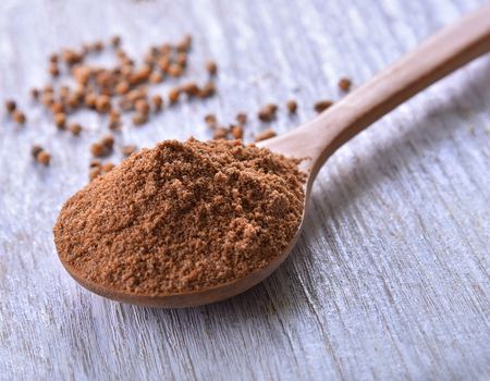 Coriander seeds powder in spoon wood on white wooden background