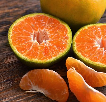 Tangerine orange fruit half cut on table wooden background Stock Photo