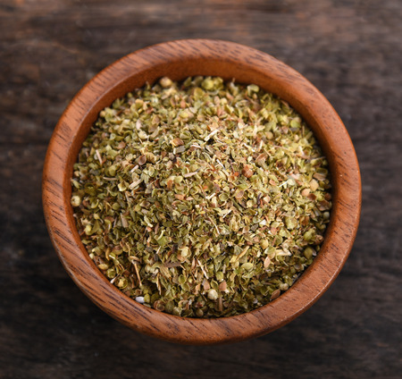 Oregano dry in wood bowl on wooden background