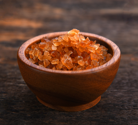 Gravel sugar in wood bowl on wooden background
