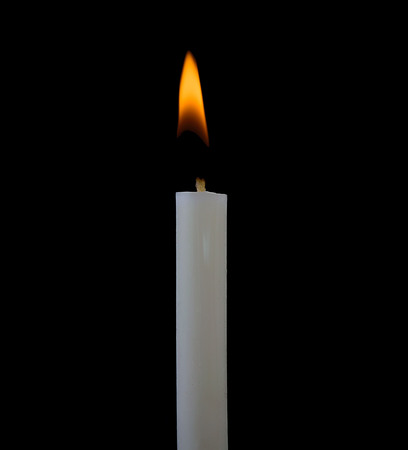vigil: One light candle burning brightly in the black background Stock Photo