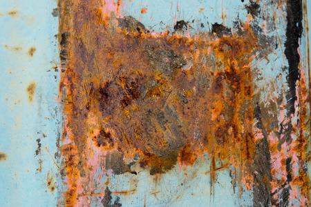 corroded: Corroded  blue metal background. Rusted white painted metal wall.