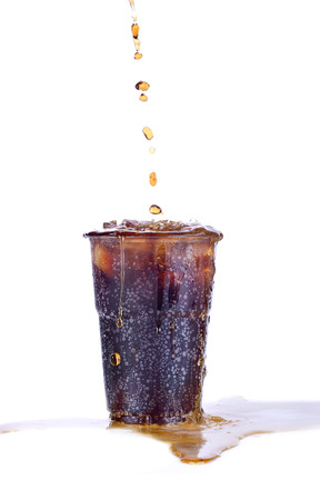 Pouring soft drink in a glass with ice on an isolated white background Stock Photo