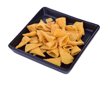 Crunchy corn snacks on black dish on a white background. Stock Photo