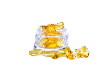 gel capsule: Omega 3 capsules for the concept of fasting in a glass cup on a white background.