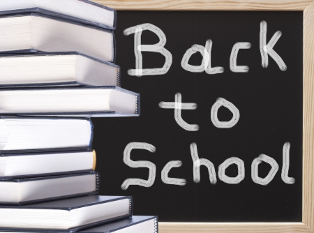 Books with back to school chalkboard text background photo
