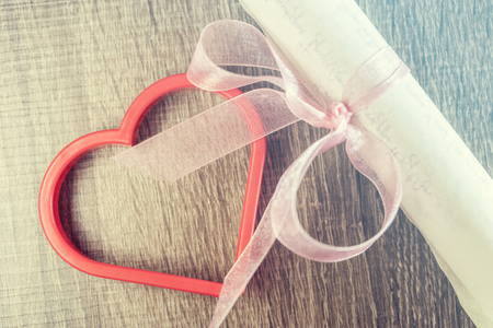 marriage: Vintage wedding invitation with pink ribbon and a red heart. Cross processed image with selective focus