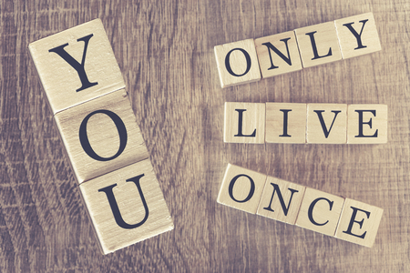 once person: You Only Live Once YOLO message written with wooden blocks on a wooden table. Image cross processed for retro look