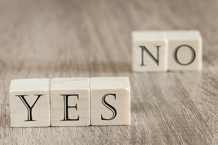 indecision: Dilemma  Decision concept. Wooden blocks forming Yes and No words. Image with selective focus Stock Photo
