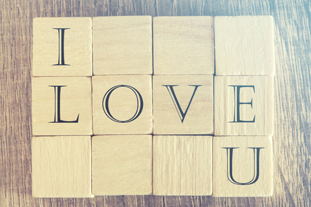 i love u: I Love U message formed with wooden blocks. Cross processed image for retro look Stock Photo