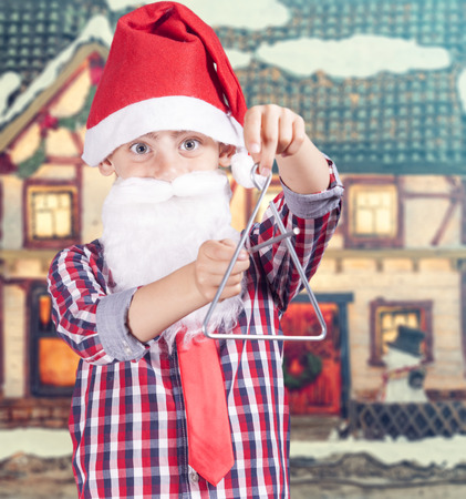 christmas carols: Cute boy dressed up as Santa playing Christmas carols with a triangle.