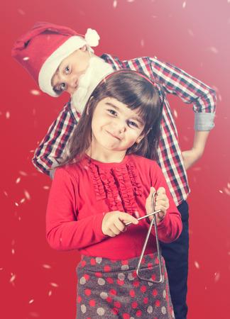 cantando: Concepto de la Navidad con el hermano y hermana cantando villancicos. Foto de archivo