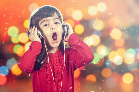 Portret niewiele Santa dziewczyna śpiewa podczas słuchania muzyki. Nieostre bokeh Boże Narodzenie światła w tle. Zdjęcie Seryjne