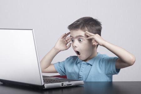 El muchacho reacciona durante el uso de un ordenador portátil. Foto de archivo