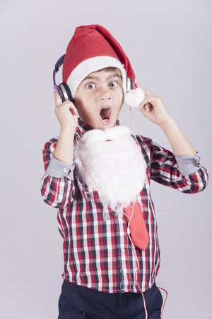 reacts: Funny little boy dressed up as Santa Claus reacts while listening to music with headphones