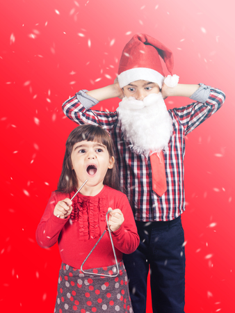 Funny Christmas concept with brother and sister singing christmas carols. Archivio Fotografico