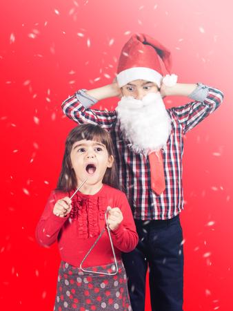 christmas carols: Funny Christmas concept with brother and sister singing christmas carols. Stock Photo