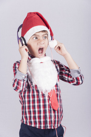 reacts: Cute little boy dressed up as Santa Claus reacts while listening to music with headphones Stock Photo