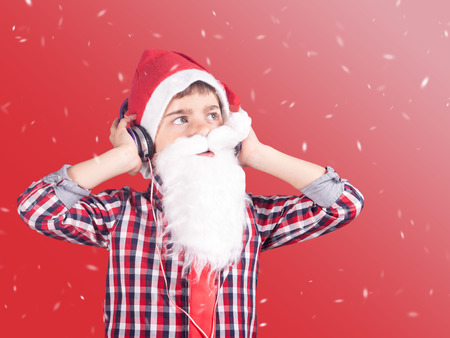 santa cross: Santa Boy listening to music with headphones. Cross processed image Stock Photo