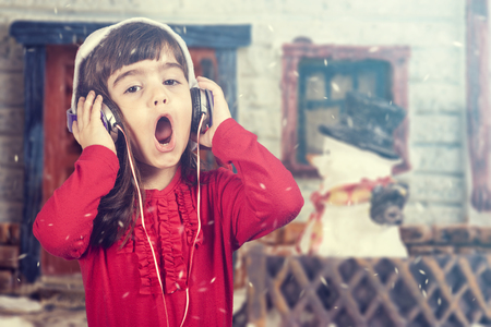 christmas hat: Adorable girl wearing a Santa hat listening to music and singing Christmas carols. Stock Photo