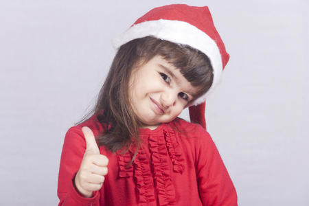 child laughing: Cute girl wearing Santa hat showing thumbs up gesture Stock Photo