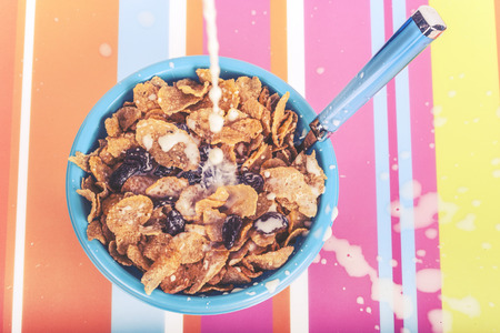 milk pouring: Milk pouring on a bowl of cereals on a colorful kitchen table. Cross processed image with shallow depth of field