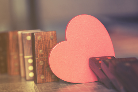 Love concept with heart stopping dominoes from falling. Selective focus image cross processed for vintage look