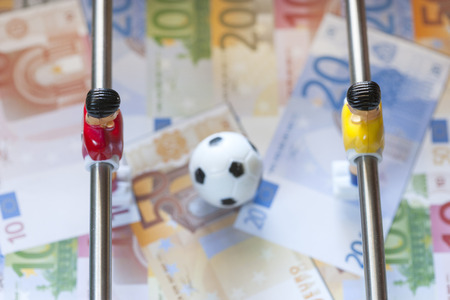 Sports and money. Concept about money spending in football soccer, sports betting and manipulated fixed matches. Selective focus image
