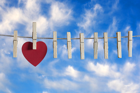 i love you sign: Love concept. Red heart hanging on a clothesline against a blue sky. Image with shallow depth of field