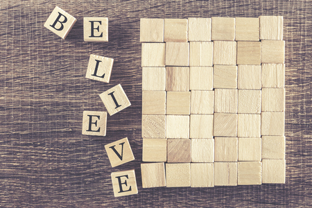 cross processed: Believe word formed with wooden blocks. Cross processed image