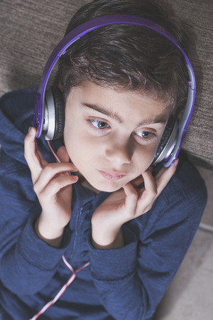 beautiful little boys: Boy listening to music. Cross processed image with shallow depth of field