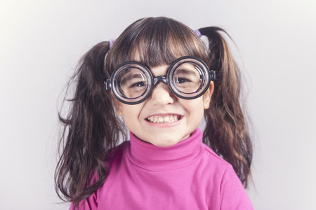 nerdy: Funny nerdy little girl smiling. Toned image with shallow depth of field