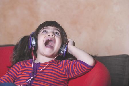 niños riendose: Niña que canta mientras se escucha música. Imagen de estilo retro filtrada con poca profundidad de campo Foto de archivo