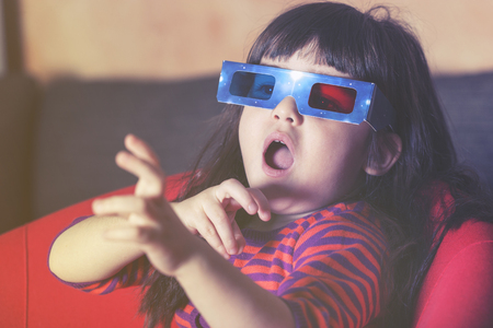 reacts: Little girl reacts while watching a 3D movie. Vintage effect image with shallow depth of field