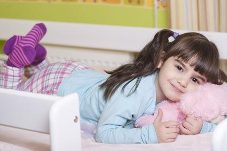 Nettes kleines Mädchen im Bett ihren Teddybären umarmt. Bild mit geringer Tiefenschärfe