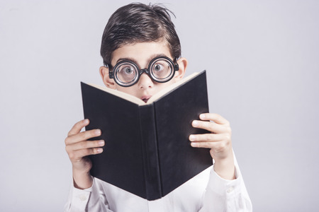 nerdy: Funny nerdy little boy reacts while reading a book. Toned image with shallow depth of field