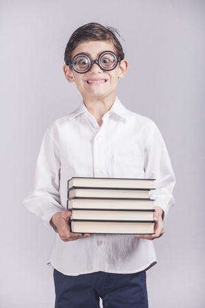 nerdy: Funny nerdy little school boy carrying his books. Toned image with shallow depth of field Stock Photo