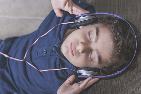 beautiful boy: Boy relaxing while listening to music. Cross processed image with shallow depth of field