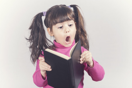 reacts: Little girl reacts while reading a book. Toned image with shallow depth of field Stock Photo