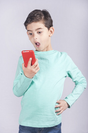 reacts: Little boy reacts while using a smart phone. Toned image with shallow depth of field