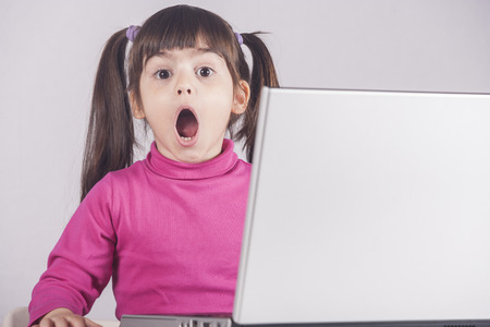 internet safety: Little girl reacts while using a laptop. Internet safety concept. Toned image with selective focus