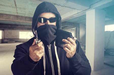 threatening: Threatening situation concept. Masked criminal holding a knife and loots. Selective focus image cross processed for dramatic look Stock Photo