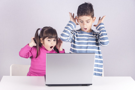 react: Little kids react with shock and awe while using a laptop. Internet safety for kids concept. Toned image with selective focus Stock Photo