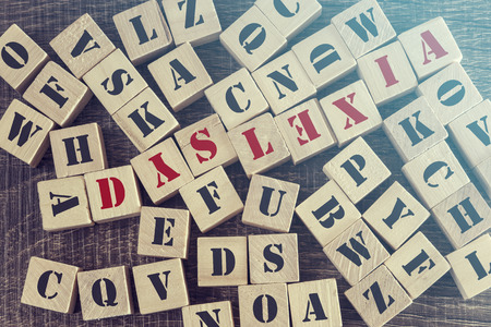 dyslexia: Dyslexia word formed with wooden blocks. Reading difficulties concept. Cross processed image with shallow depth of field