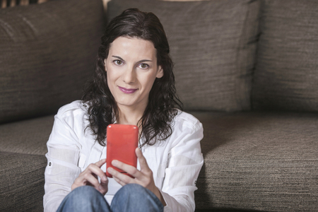 Attractive middle aged woman sitting on the sofa at home using a smart phone