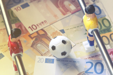 Sports and money. Concept about money spending in football (soccer), sports betting and manipulated fixed matches. Selective focus image cross processed for retro look