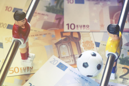 manipulated: Sports and money. Concept about money spending in football (soccer), sports betting and manipulated fixed matches. Selective focus image cross processed for retro look