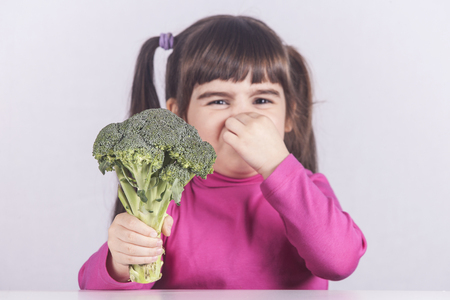 Little girl making a funny face refusing to eat her vegetables Standard-Bild