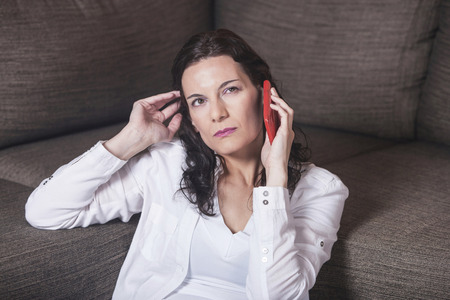40 year old woman: Woman receiving bad news while talking on the phone